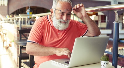 cheerful senior man raised his glasses and looking at laptop in cafe