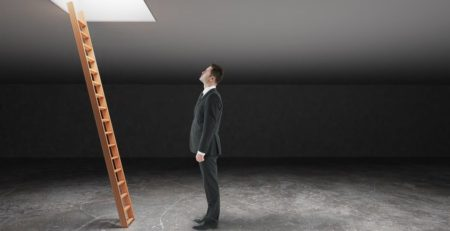 Businessman looking at wooden ladder in dark grey basement leading out to light. Freedom concept. 3D Rendering